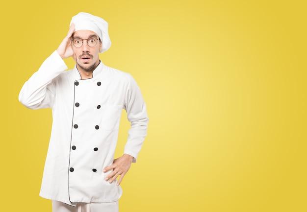 Besorgter junger koch, der aufwirft