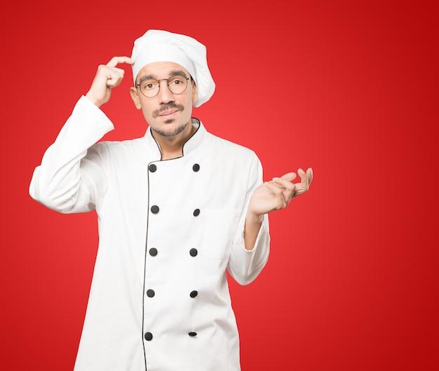 Besorgter junger koch, der eine geste der verwirrung tut