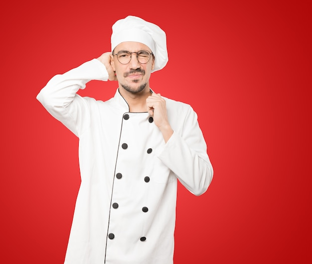 Besorgter junger koch, der eine geste des stresses tut