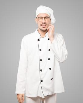 Besorgter junger koch, der eine kratzende geste macht