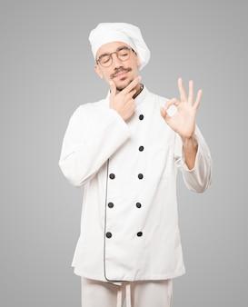 Besorgter junger koch, der zweifelt und eine geste der zustimmung macht