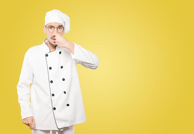 Besorgter junger koch mit einer geste des ekels