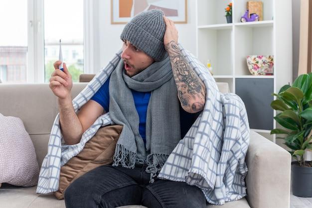 Besorgter junger kranker mann mit schal und wintermütze, der in decke gewickelt auf dem sofa im wohnzimmer sitzt und das thermometer hält und die hand auf dem kopf hält