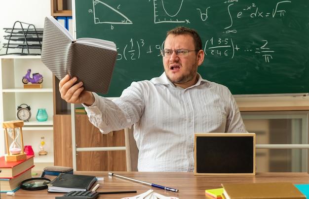 Besorgter junger lehrer mit brille, der am schreibtisch mit schulmaterial und einer mini-tafel darauf im klassenzimmer sitzt und einen notizblock ausstreckt, der darauf schaut?