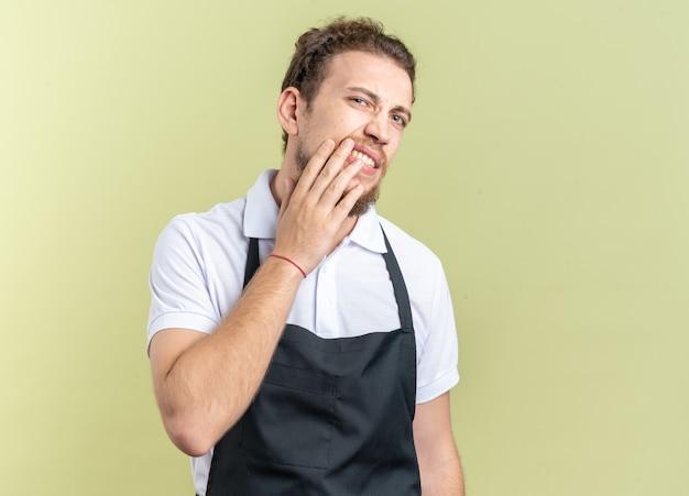 Besorgter junger männlicher friseur mit uniform bedeckte den mund mit der hand isoliert auf olivgrüner wand