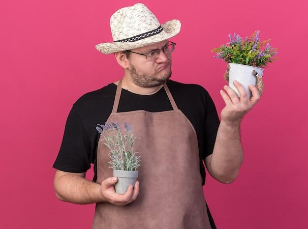 Besorgter junger männlicher gärtner mit gartenhut, der blumen in blumentöpfen hält und anschaut, isoliert auf rosa wand