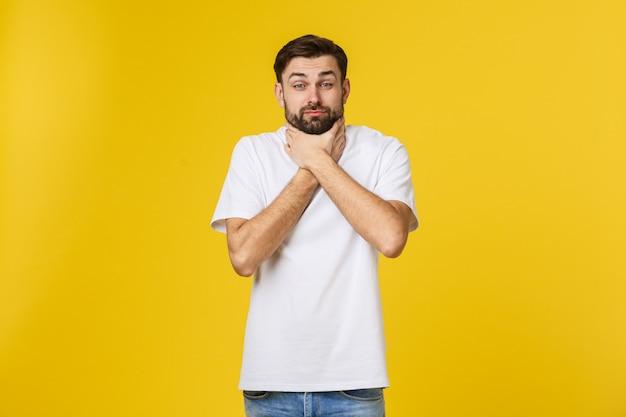 Besorgter junger mann, der isolat auf gelber wand steht