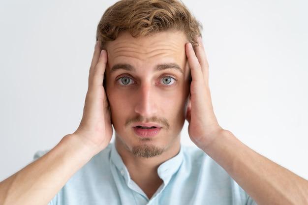 Besorgter junger mann, der kamera betrachtet und kopf berührt