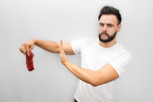 Besorgter junger mann steht und hält stück fleisch. es ist schlecht. junger mann zeigt stoppsymbol mit der hand. er sieht und posiert.