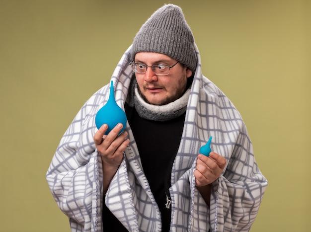 Besorgter kranker mann mittleren alters mit wintermütze und schal, der in kariertes halten gewickelt ist und einläufe ansieht