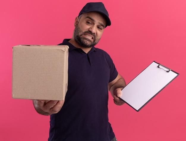 Besorgter lieferbote mittleren alters in uniform und mütze, die zwischenablage hält und die box an der kamera isoliert auf rosa wand hält