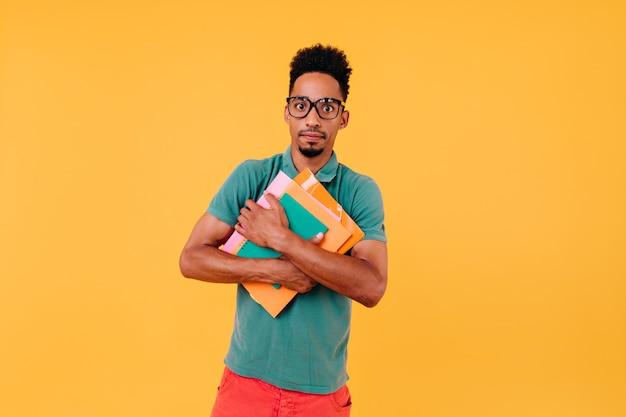 Besorgter männlicher student, der seine bücher hält. innenaufnahme des afrikanischen jungen in den gläsern und im grünen t-shirt, die für prüfungen vorbereiten.