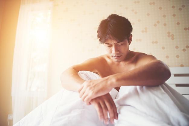 Besorgter mann, der morgens auf bett, ernstes denkendes etwas sitzt