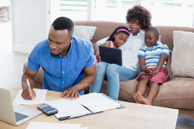 Besorgter mann, der rechnungen berechnet, während seine frau und kinder digitales tablett auf sofa verwenden