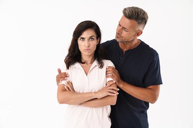 Besorgter mann, der versucht, seine freundin zu trösten, während er isoliert über weißer wand steht?