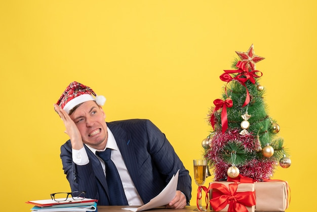 Besorgter mann mit weihnachtsmütze, der am tisch nahe weihnachtsbaum sitzt und auf gelb präsentiert