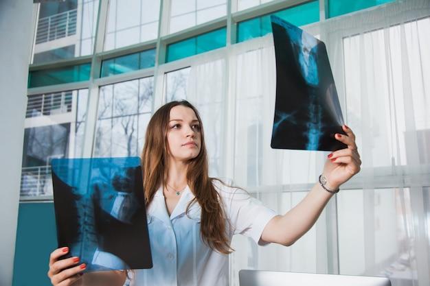 Besorgter medizinischer arbeiter mit röntgenaufnahme des patienten. ärztin in der klinik untersucht den menschlichen schädel röntgen. medizin service head desease gesundheitskonzept.
