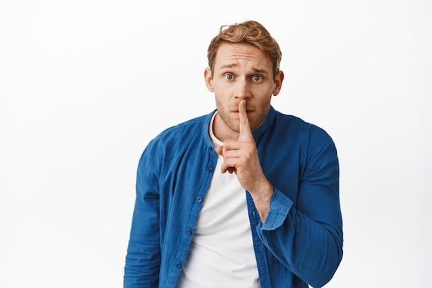 Besorgter rothaariger mann, der darum bittet, ruhig zu bleiben, ein geheimnis zu haben, mit dem finger auf die lippen gedrückt zu werden, mit nervösem ausdruck ein psst-stummzeichen zu machen, zu betteln, tabu zu bleiben, weiße wand