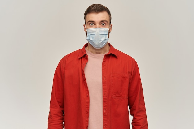 Besorgter schockierter junger bärtiger mann im roten hemd und in der virusschutzmaske im gesicht gegen coronavirus, das vorne über weißer wand steht und schaut