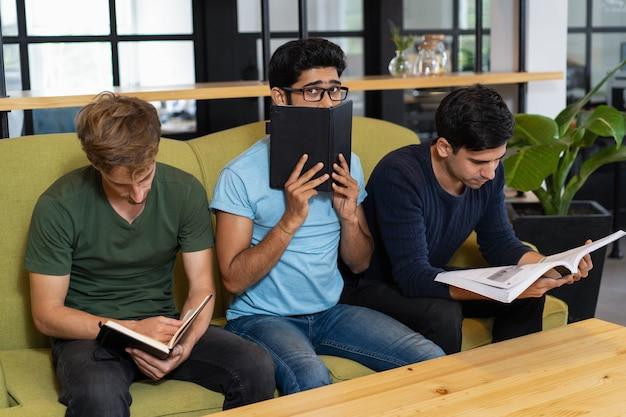 Besorgter student, der hinter notizbuch und sitzen sich versteckt