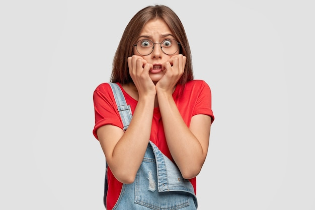 Besorgter teenager mit brille, die gegen die weiße wand aufwirft
