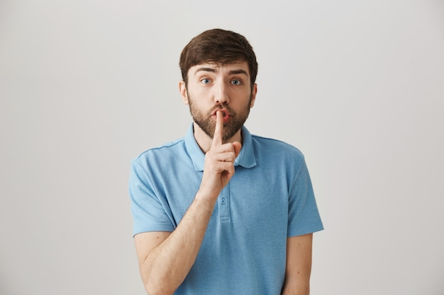 Besorgter und besorgter junger bärtiger mann posiert