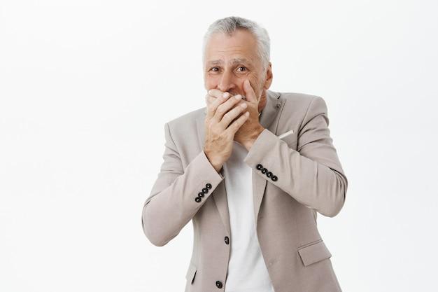 Besorgter und schockierter älterer mann bedeckt den mund mit den händen und sieht besorgt aus