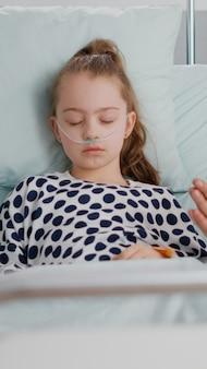Besorgter vater, der für die gesundheit der kranken mädchentochter betet, nachdem er eine medizinische operation in der krankenstation erlitten hatte. kleines kind mit sauerstoff-nasenschlauch, der während der krankheitsuntersuchung schläft