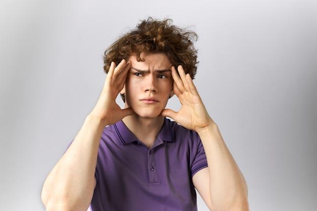 Besorgter, verärgerter junger mann mit lockigem haar, der müde aussieht und die schläfen massiert, um die schmerzen zu lindern, während er an migräne oder kopfschmerzen leidet. trauriger kerl, der wegen problemen depressiv ist