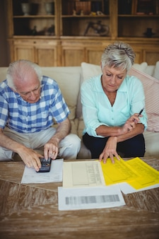 Besorgtes älteres paar, das rechnungen im wohnzimmer überprüft