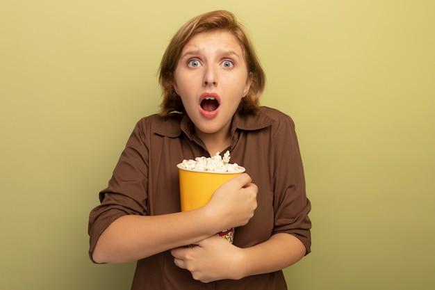 Besorgtes junges blondes mädchen, das eimer popcorn umarmt und auf olivgrüner wand mit kopienraum isoliert ist