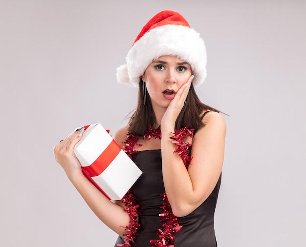 Besorgtes junges hübsches kaukasisches mädchen mit weihnachtsmütze und lametta-girlande um den hals, das in die kamera schaut, die ein geschenkpaket hält, das die hand auf dem gesicht hält, isoliert auf weißem hintergrund mit kopierraum