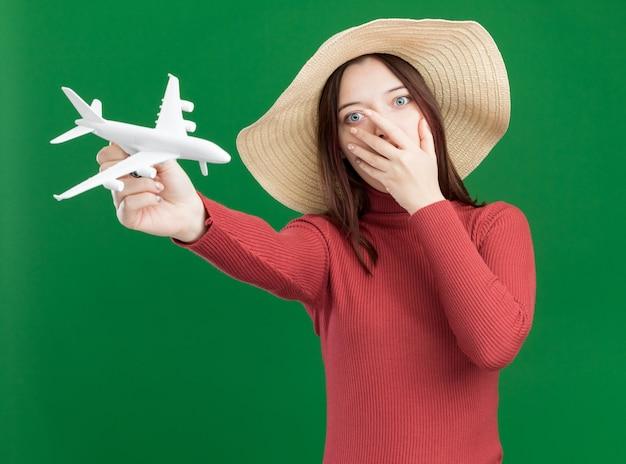 Besorgtes junges hübsches mädchen mit strandhut, das das modellflugzeug ausstreckt und die hand auf dem mund hält