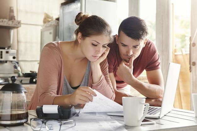 Besorgtes junges kaukasisches ehepaar, das wichtige benachrichtigungen von der bank liest, während es die inländischen finanzen verwaltet und ihre ausgaben am küchentisch unter verwendung eines laptops und eines taschenrechners berechnet