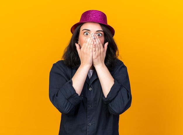 Besorgtes junges kaukasisches partymädchen mit partyhut, das die hände auf den mund hält und nach vorne isoliert auf oranger wand mit kopierraum schaut