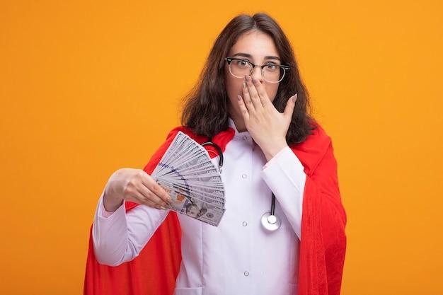 Besorgtes junges kaukasisches superheldenmädchen in arztuniform und stethoskop mit brille, das geld hält und die hand auf den mund legt