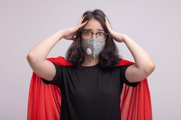 Besorgtes junges kaukasisches superheldenmädchen in rotem umhang mit brille und schutzmaske, das die hände auf dem kopf isoliert auf weißer wand hält