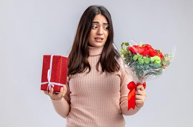 Besorgtes junges mädchen am valentinstag mit geschenkbox und blick auf blumenstrauß in der hand isoliert auf weißem hintergrund