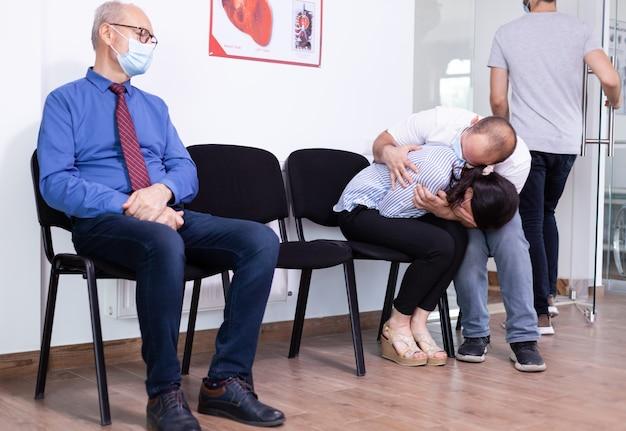 Besorgtes junges paar, das gesichtsmaske gegen eine infektion mit coronavirus trägt, während es auf nachrichten vom arzt wartet