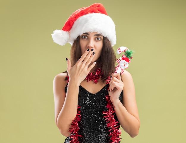 Besorgtes junges schönes mädchen, das weihnachtsmütze mit girlande am hals trägt und weihnachtsspielzeug bedeckten mund mit der hand isoliert auf olivgrünem hintergrund hält