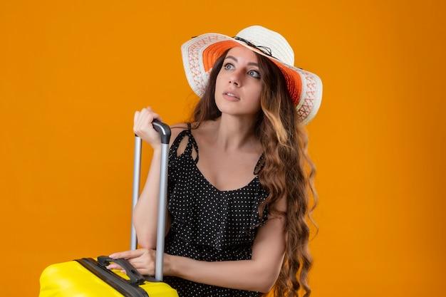 Besorgtes junges schönes mädchen im kleid im tupfen im sommerhut, der mit koffer steht, der über gelbem hintergrund beiseite schaut