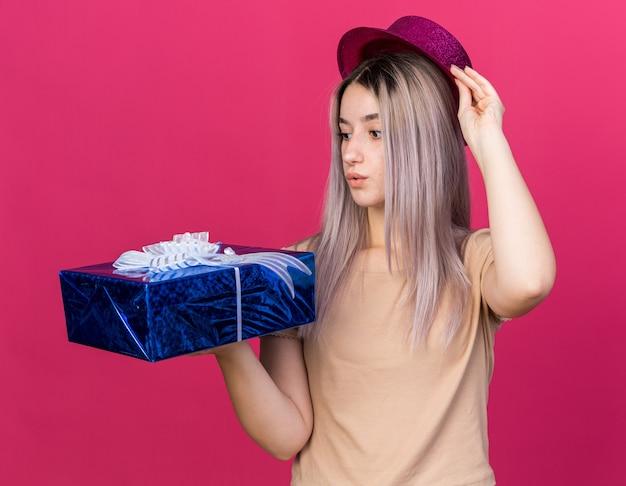 Besorgtes junges schönes mädchen mit partyhut, das geschenkbox hält und betrachtet