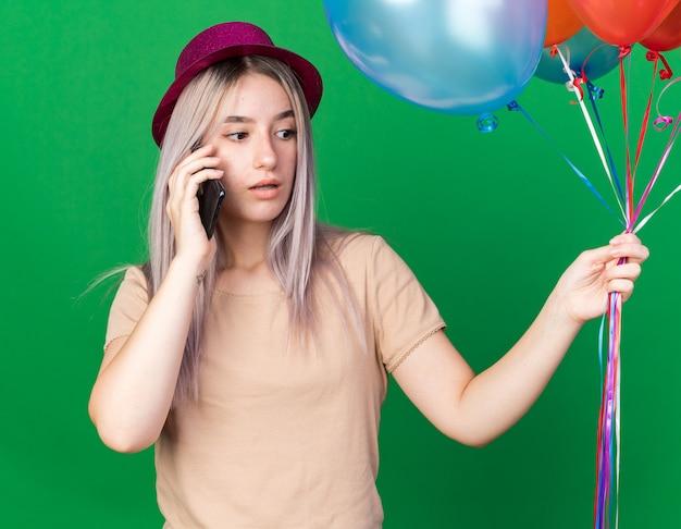 Besorgtes junges schönes mädchen mit partyhut, das luftballons spekas am telefon hält