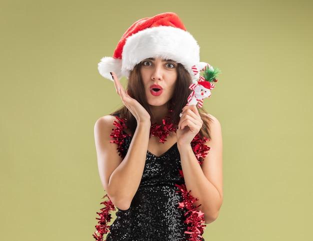 Besorgtes junges schönes mädchen mit weihnachtsmütze mit girlande am hals, das weihnachtsspielzeug isoliert auf olivgrünem hintergrund hält