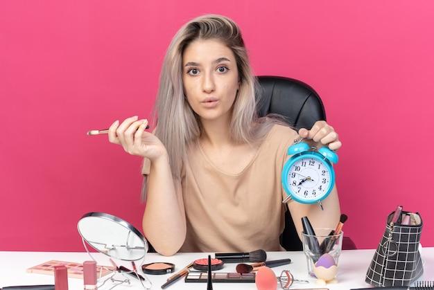 Besorgtes junges schönes mädchen sitzt am tisch mit make-up-tools und hält wecker isoliert auf rosa wand