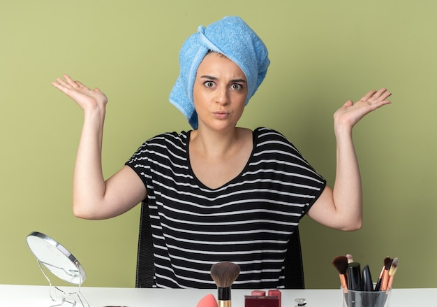 Besorgtes junges schönes mädchen sitzt am tisch mit make-up-werkzeugen, die haare in handtuch wickeln, die hände isoliert auf olivgrüner wand ausbreiten?