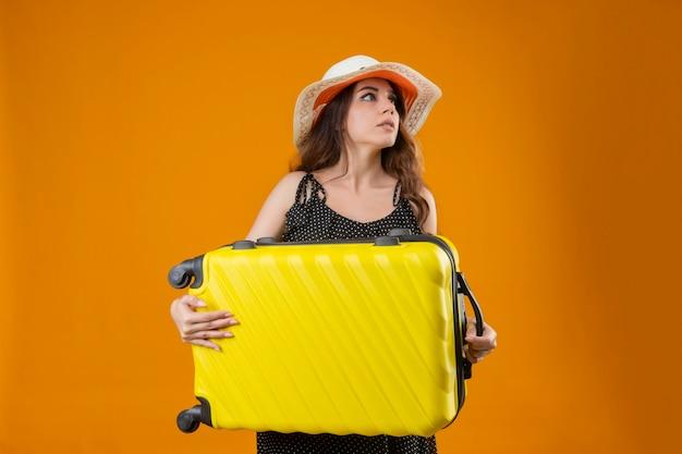 Besorgtes junges schönes reisendes mädchen im kleid im tupfen im sommerhut, der koffer hält, der beiseite steht über gelbem hintergrund
