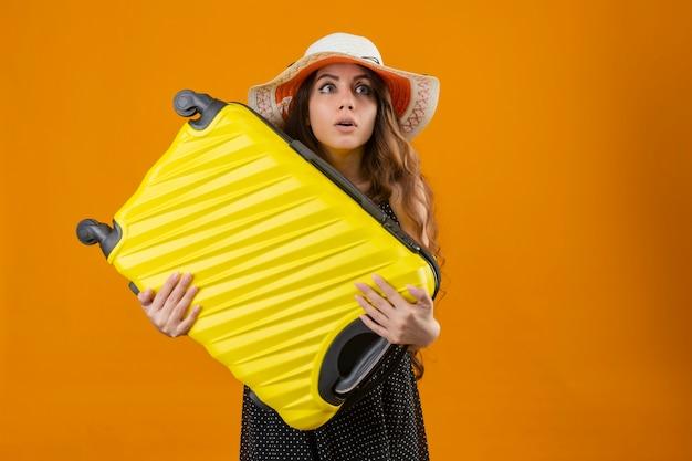 Besorgtes junges schönes reisendes mädchen im kleid im tupfen im sommerhut, der koffer hält, der beiseite steht über orange hintergrund