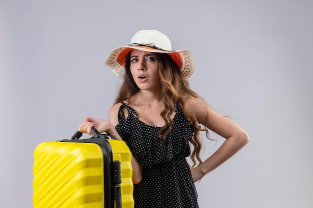 Besorgtes junges schönes reisendes mädchen im kleid im tupfen im sommerhut, der koffer hält kamera betrachtet über weißem hintergrund