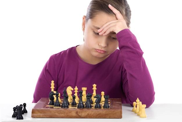 Besorgtes kleines mädchen, das schach auf über weißem hintergrund spielt